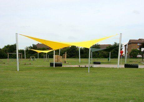 На фото: Стильные навесы для зоны отдыха на территории спортивной детской площадки Паруса теневые тенты